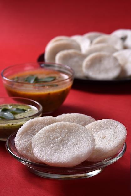 Idli、サンバルとココナッツチャツネ、インド料理:南インドのお気に入りの食べ物ラバイドゥリまたはセモリナを無造作または無造作に、サンバーとグリーンチャツネを添えて。 Premium写真