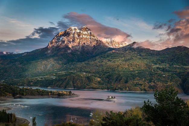 Ripresa idilliaca di un'enorme montagna ricoperta di vegetazione con uno specchio d'acqua alla sua base Foto Gratuite