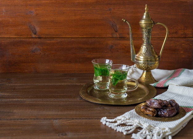 Iftarとsuhoorラマダンの概念、ガラスのカップにメンタ茶、古いティーポットと木の日付 Premium写真