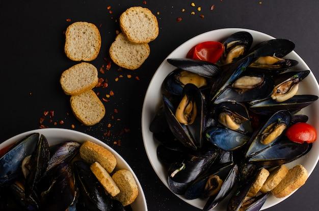 ムール貝のスープは黒の背景にトマト、唐辛子、ぱりっとしたパンとワインで蒸しました。 iitalianシーフード。フラット横たわっていた、トップビュー、コピースペース Premium写真