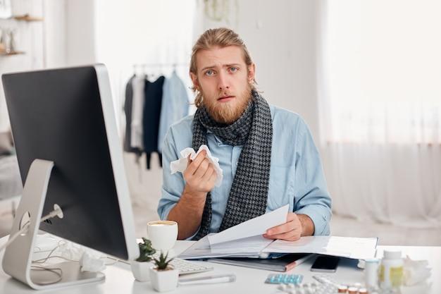 Больной бородатый человек чихает, использует платок, плохо себя чувствует, болен гриппом. больной мужчина офисного работника имеет жар и усталость, обсуждает рабочие вопросы с коллегами. концепция болезни и инфекции Бесплатные Фотографии