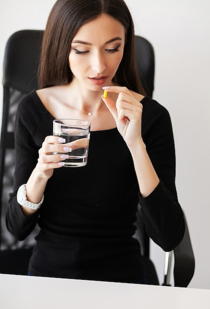 病気の実業家が不平を言って、オフィスで薬を飲んでいます。 Premium写真