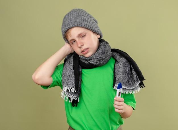 暖かいスカーフと帽子で緑のtシャツを着ている病気の少年は、明るい背景の上に立って不幸で病気のカメラを見て体温計を持って気分が悪い 無料写真