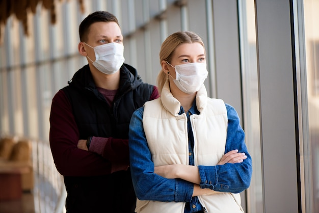 Ill man and woman feeling sick, wearing protective mask against transmissible infectious diseases and as protection against the flu. Premium Photo