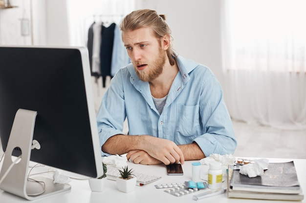 Ill or sick bearded male dressed in blue shirt with tired and suffering face expression, being allergic, having health problems.young man has running nose, sits at workplace with pills and drugs Free Photo