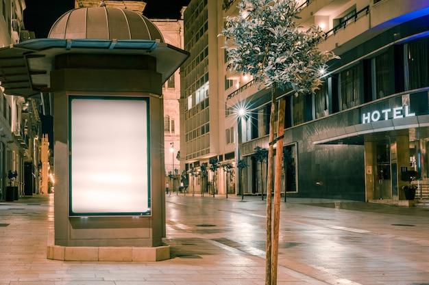 Un cartellone illuminato vicino alla strada Foto Gratuite