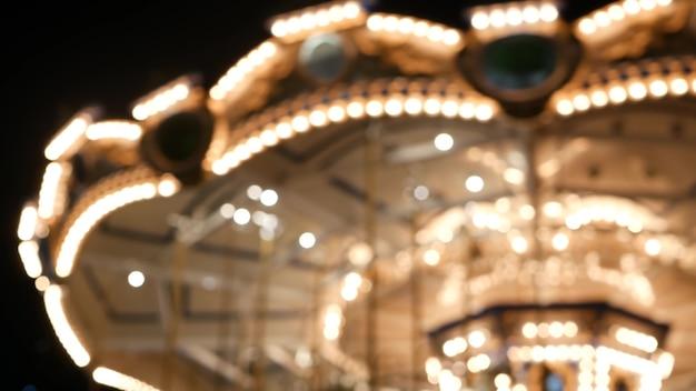 照らされたぼやけたメリーゴーランド。ラウンドアバウトの回転、夜の遊園地のカルーセルライト。 Premium写真