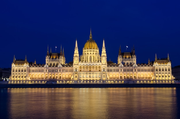 Illuminated budapest hungarian parliament at night reflected in the danube river. Premium Photo