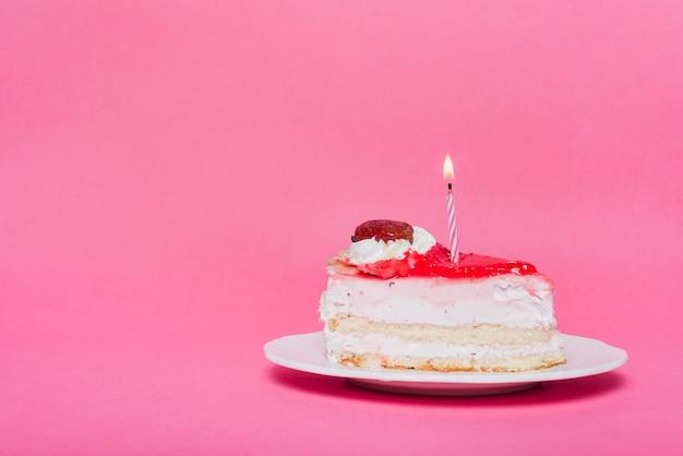Awesome Illuminated Candle On Birthday Cake Slice With Pink Background Personalised Birthday Cards Akebfashionlily Jamesorg