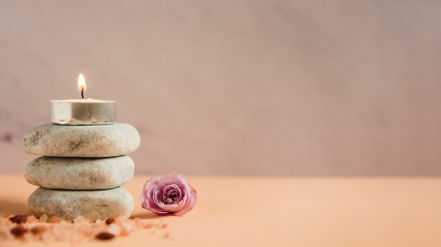 Illuminated candle over the stack of spa stones with himalayan salts and pink rose on colored background Free Photo
