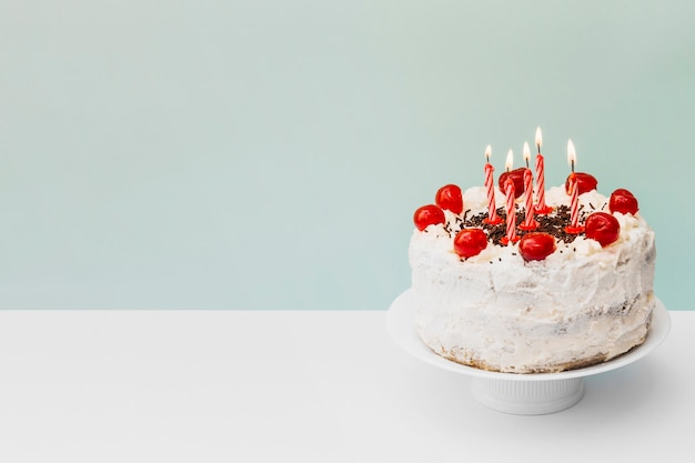 Illuminated candles on birthday cake on cake stand against blue background Free Photo