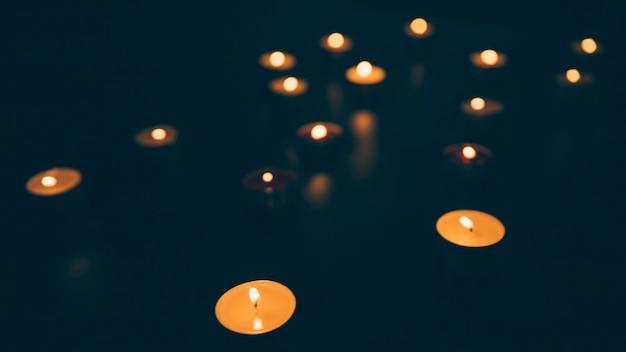 Illuminated candles on black background Free Photo