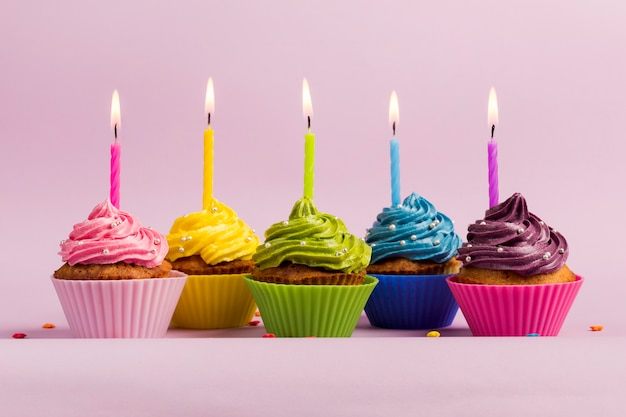 An illuminated candles over the colorful muffins against pink backdrop Free Photo