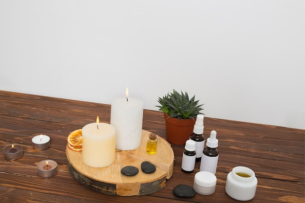An illuminated candles; dried citrus slices; la stone; honey and essential oil bottles on pot plant over the desk against wall Free Photo