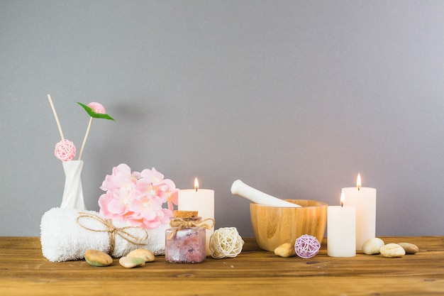 Illuminated candles; scrub bottles; flower; spa stones; mortar and pestle on wooden tabletop Free Photo