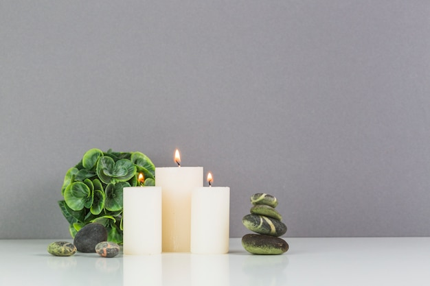 Illuminated candles; spa stones and green leaves in front of grey wall Free Photo