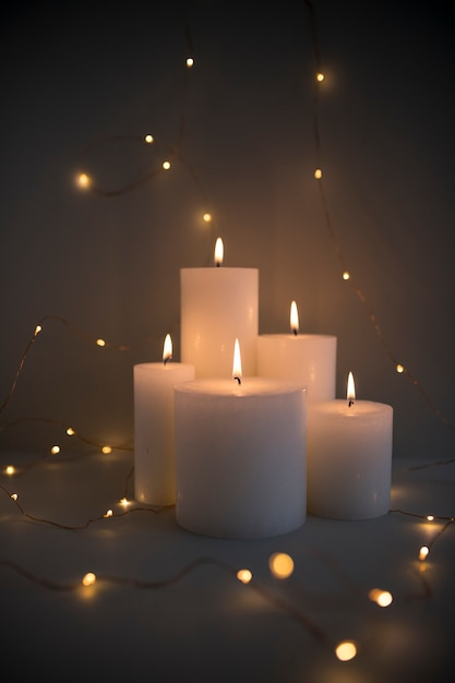 Illuminated candles surrounded with glowing fairy lights on dark background Free Photo
