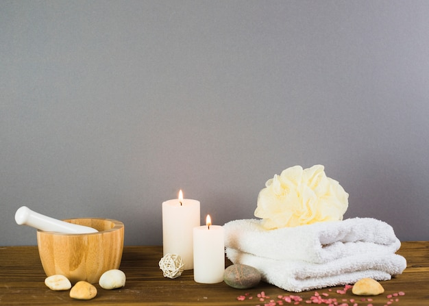 Illuminated candles; towel; spa stones; loofah; mortar and pestle on wooden surface Free Photo