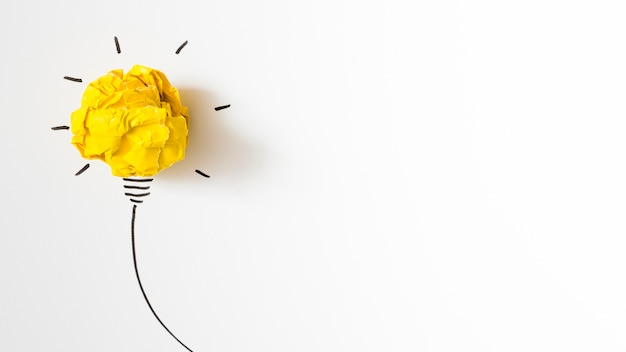 Illuminated crumpled yellow paper light bulb idea on white background Free Photo