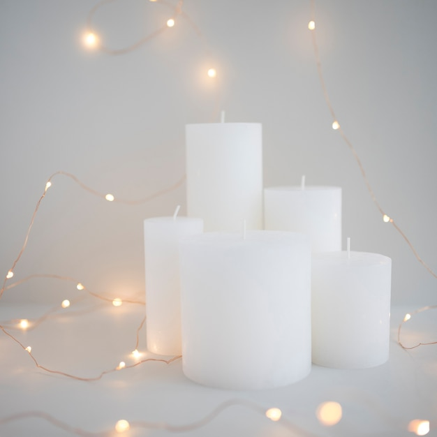 Illuminated fairy lights around white candles on grey background Free Photo
