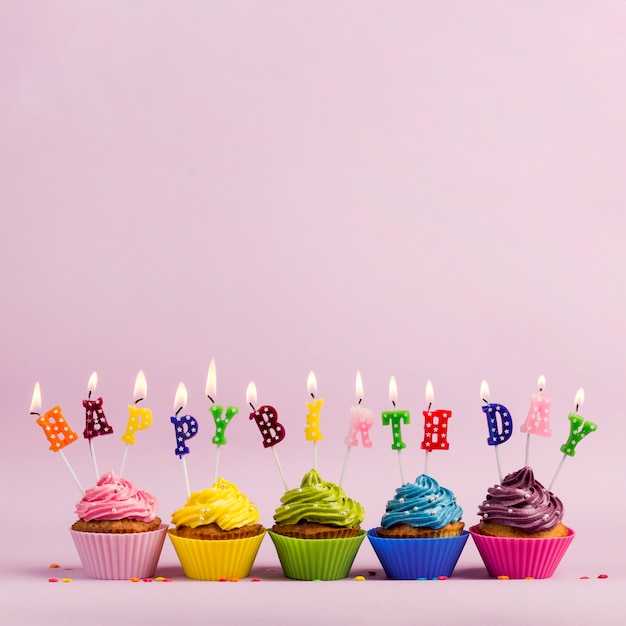 An illuminated happy birthday text candles over the colorful muffins against pink backdrop Free Photo