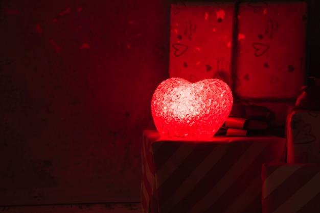 Lampada illuminata a forma di cuore vicino a scatole attuali Foto Gratuite