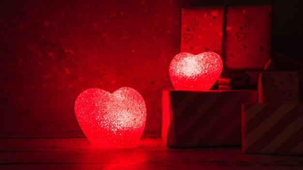 ギフトボックスの近くの心臓の形のイルミネーションランプ 無料写真