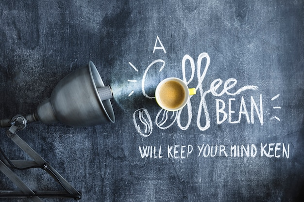 Illuminated light bulb over the coffee cup and text on blackboard Free Photo