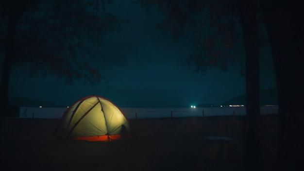 Освещенная палатка на пляже под красивым таинственным ночным небом Бесплатные Фотографии