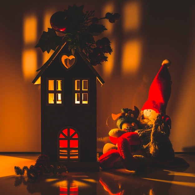 Illuminated wooden house with rag dolls Free Photo