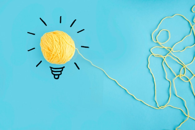 Illuminated yarn yellow light bulb on blue background Free Photo