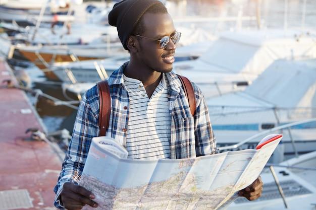 Immagine di un uomo africano in viaggio, in piedi nel mezzo del porto in attesa dei suoi amici, con in mano una mappa cartacea, con aria eccitata e allegra, in attesa di nuove impressioni ed esperienze Foto Gratuite