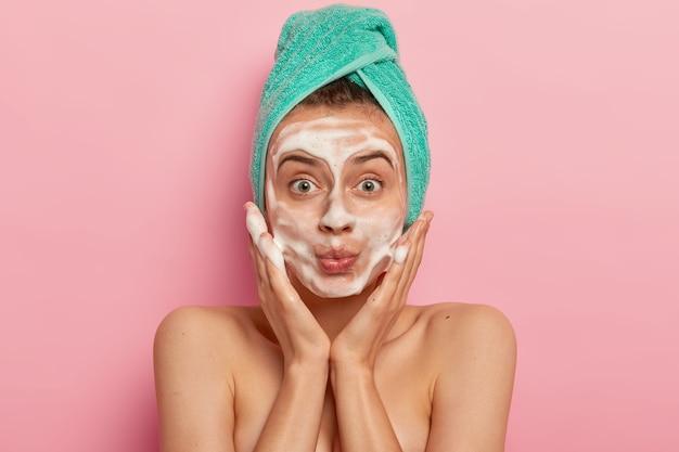 L'immagine di una donna attraente si lava il viso con la schiuma, massaggia le guance, si guarda sorprendentemente, indossa un asciugamano avvolto sulla testa, rimuove lo sporco, sente la freschezza dopo la doccia, i modelli al coperto Foto Gratuite