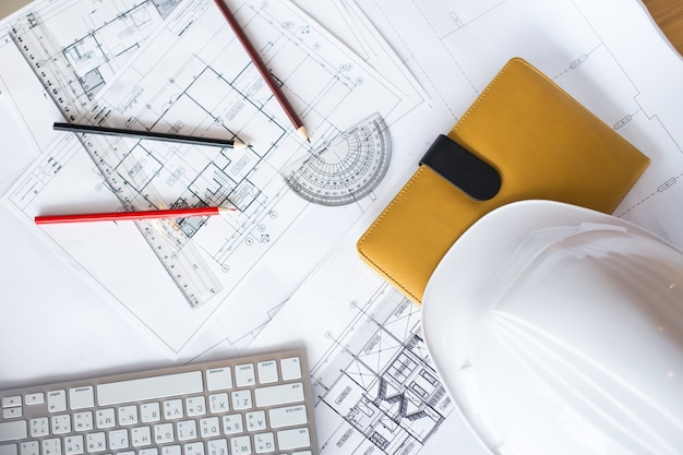Image of blueprints with level pencil and hard hat on table Free Photo