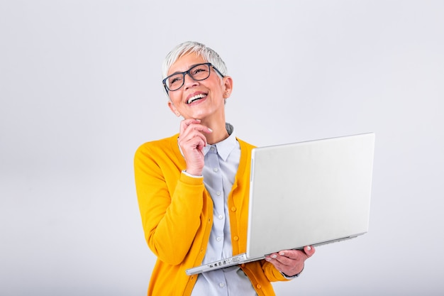 Image of cheerful mature woman standing isolated over gray background using laptop computer. portrait of a smiling senior lady holding laptop computer Premium Photo