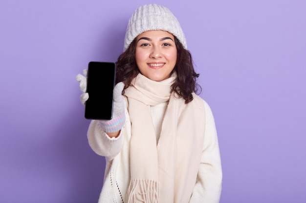 Image of delighted attractive model holding her switched off smartphone in one hand, showing it, blank screen, being in good mood, looking directly at camera, isolated on lilac. Free Photo