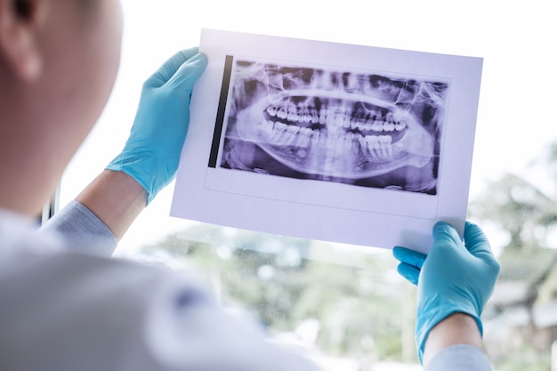 Image of doctor or dentist holding and looking at dental x-ray Premium Photo