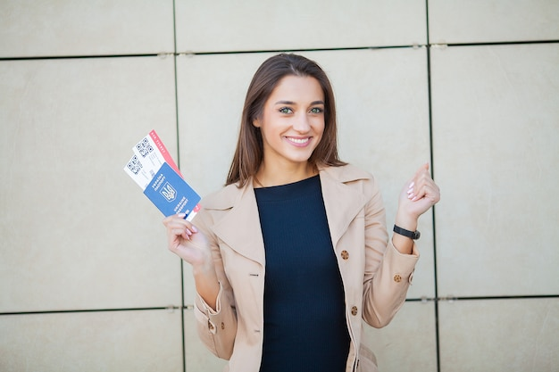 Image of european woman having beautiful brown hair smiling while holding passport and air tickets Premium Photo