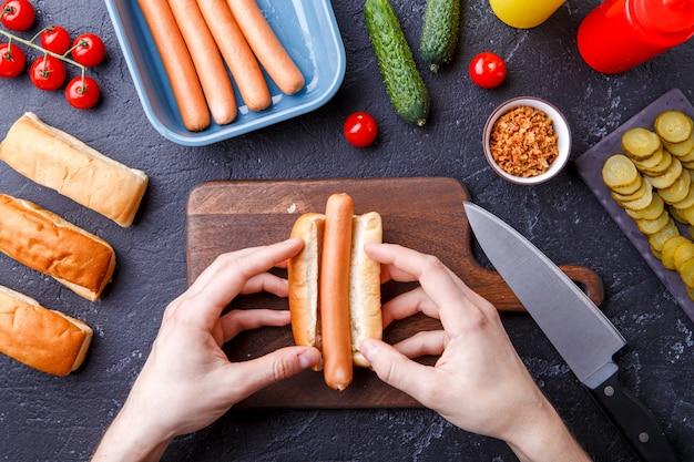 Изображение сверху человека, делающего хот-доги на столе Premium Фотографии