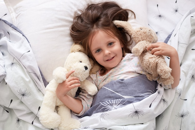 Hay Hay Chicken Stuffed Animal, Premium Photo Image Of Girl Lying With Fluffy Teddy Bear And Dog Before Giving Them Big Hug Beautiful Kid Relaxing In Bed With Her Toy