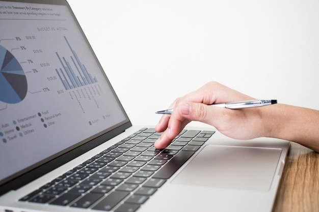 The image of the hand of the businessman creating financial graph data on the laptop. Premium Photo