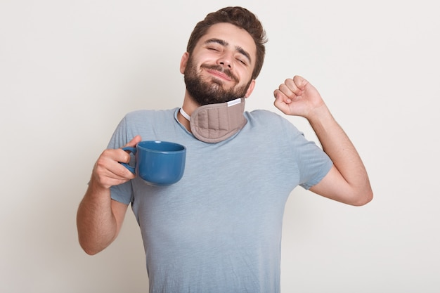 Image of handsome male has morning coffee, still sleeps, yawns, standing indoor isolated over white Free Photo