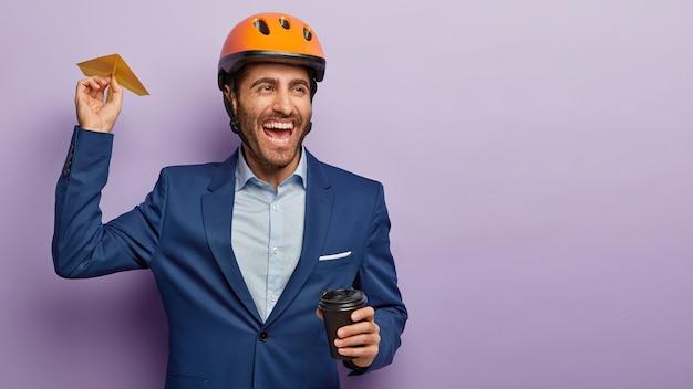 Immagine di felice ingegnere maschio spensierato lancia un aereo fatto a mano, beve caffè, felice di raggiungere il successo sul lavoro, guarda lontano e ride Foto Gratuite