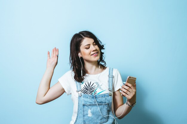 Image of happy woman wearing earphones singing isolated over blue wall Premium Photo