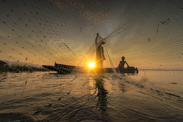 Image is silhouette. fishermen casting are going out to fish early in the morning with wooden boats, old lanterns and nets. concept fisherman's life style. Premium Photo
