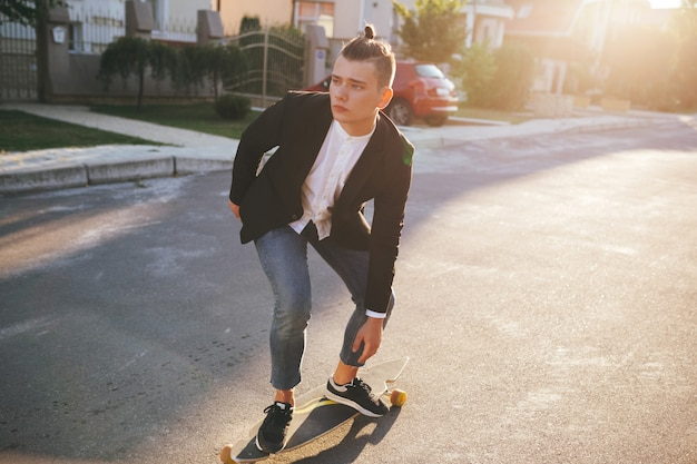 Image of a man with longboard going on road Free Photo