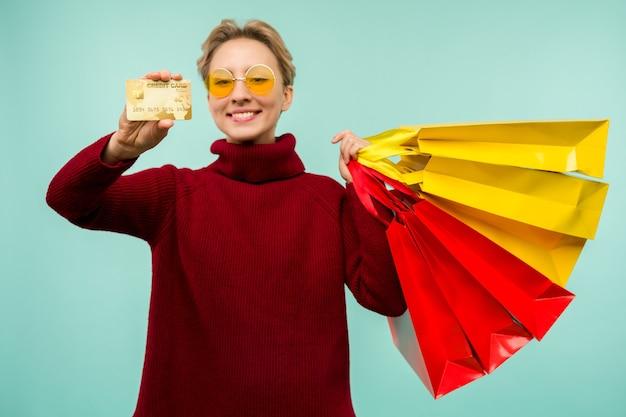 쇼핑백과 신용 카드를 들고 아름 다운 행복 한 젊은 금발의 여자의 이미지 프리미엄 사진