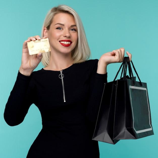 쇼핑 가방을 들고 파란색 벽 공간에 고립 된 포즈 아름 다운 행복 한 젊은 금발의 여자의 이미지. 검은 금요일 휴가 개념. 판매 프리미엄 사진
