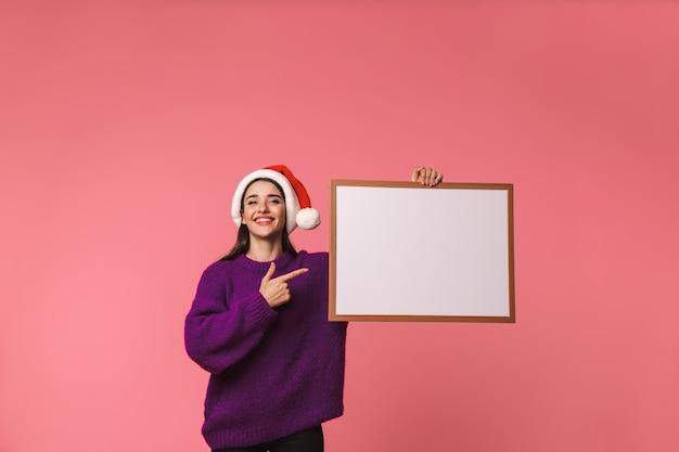 아름 다운 행복 한 젊은 감정적 인 여자의 이미지는 핑크 Copyspace 빈 포인팅을 들고 이상 격리 포즈. 프리미엄 사진