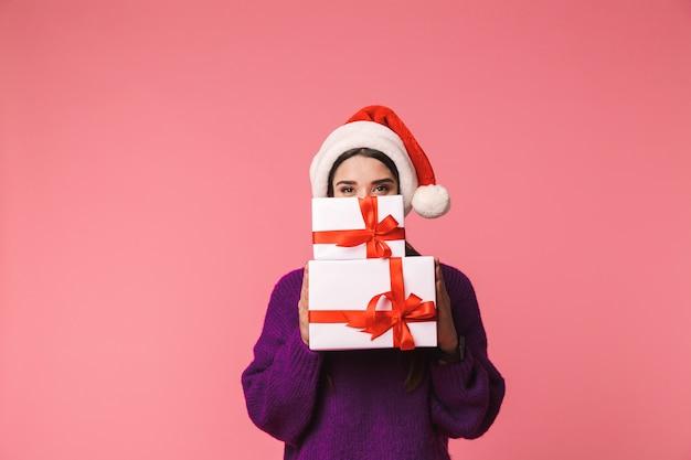 아름 다운 행복 한 젊은 감정적 인 여자의 이미지는 얼굴을 덮고 크리스마스 모자를 쓰고 선물 상자를 들고 핑크 이상 격리 포즈. 프리미엄 사진